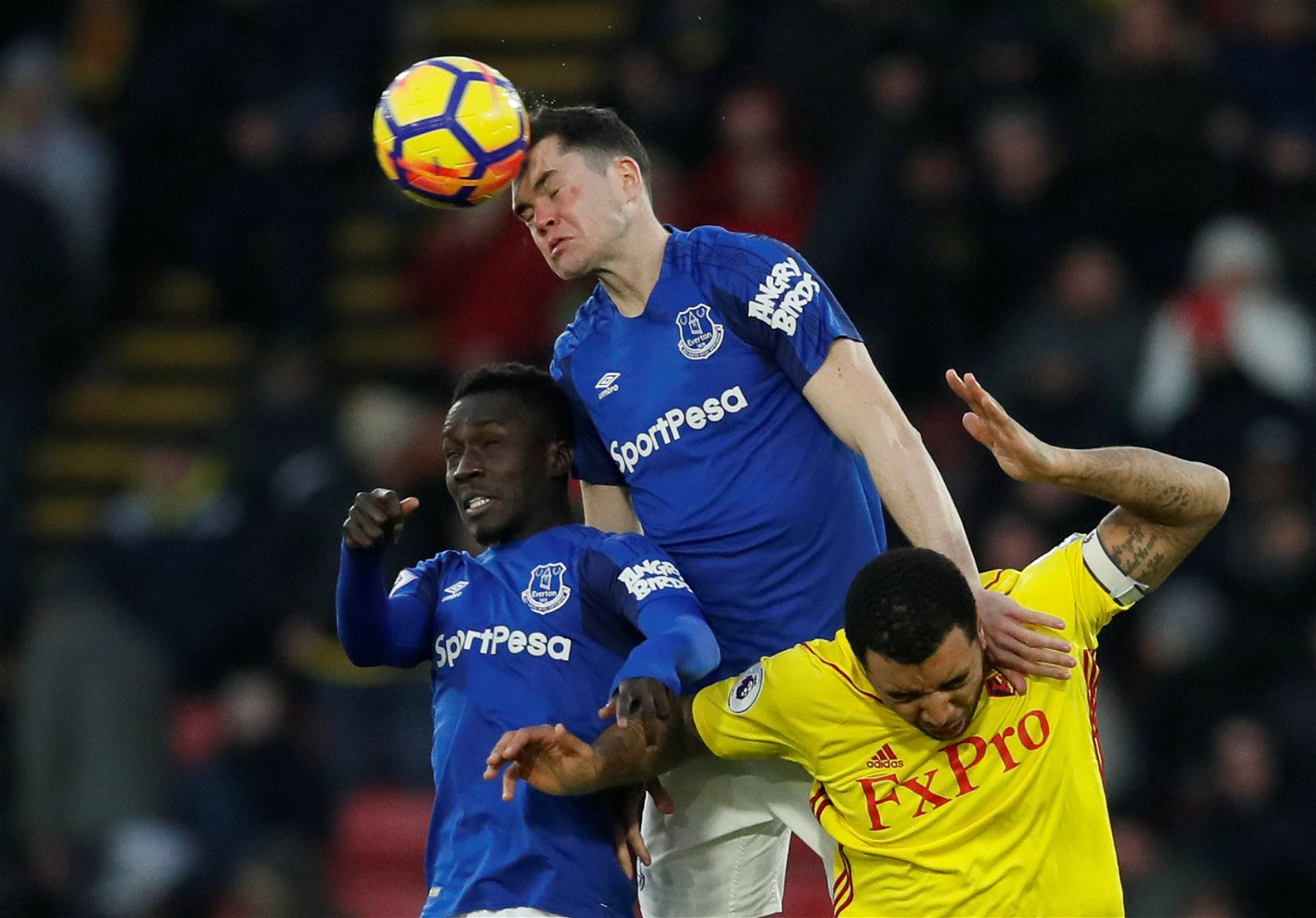 Michael Keane challenges for the ball in the air