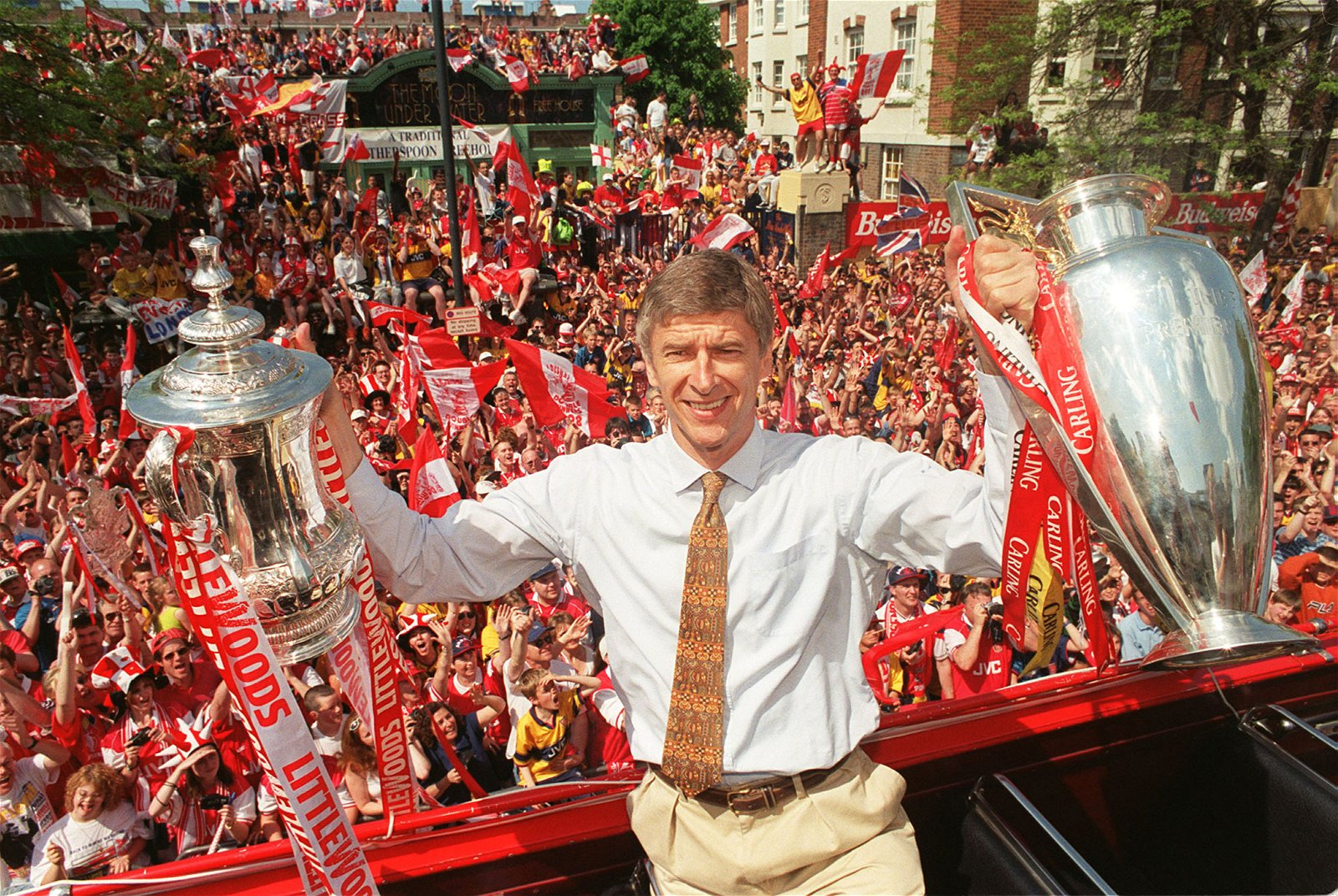 Arsene Wenger with Premier League and FA Cup trophies