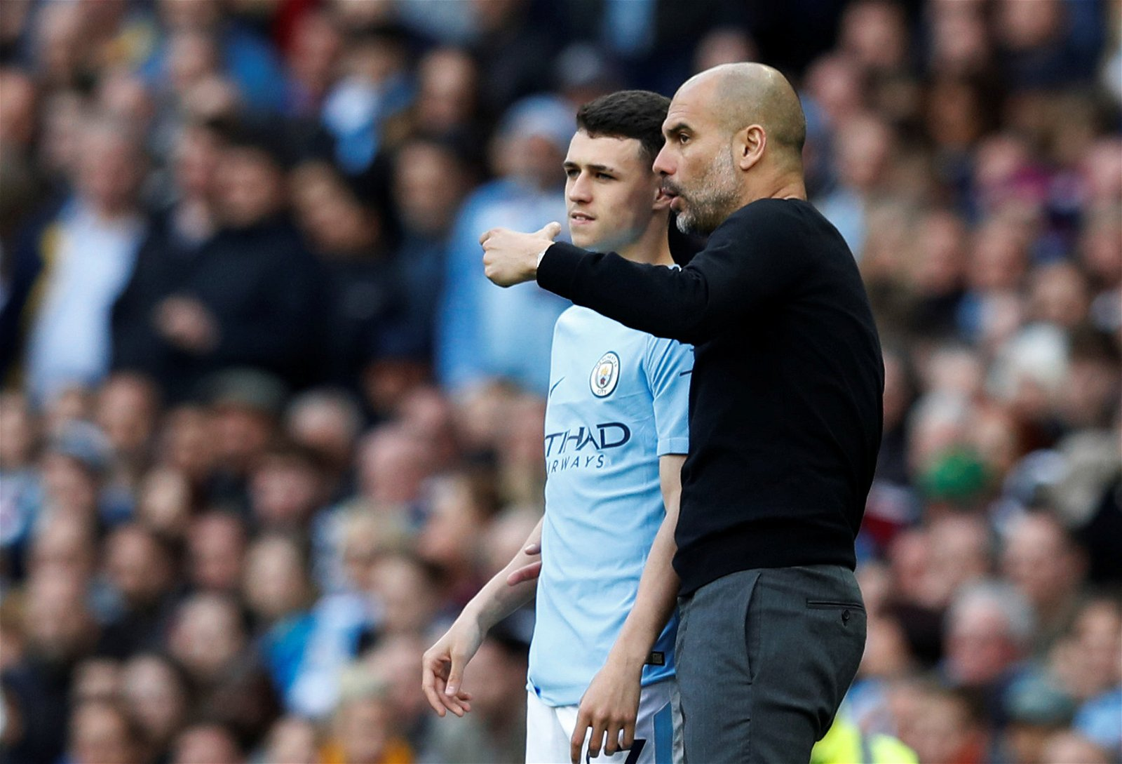 Manchester City boss Pep Guardiola gives Phil Foden instructions on the touchline