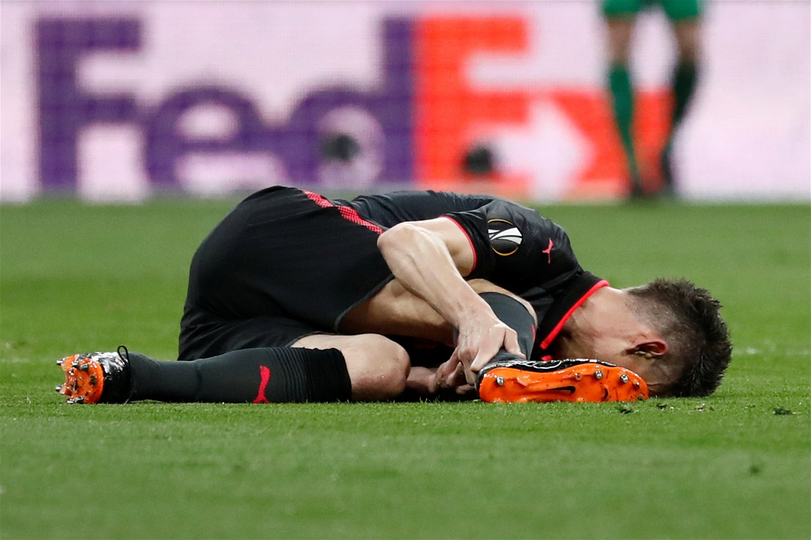 Laurent Koscielny suffers an injury during Arsenal's Europa League match against Atletico Madrid