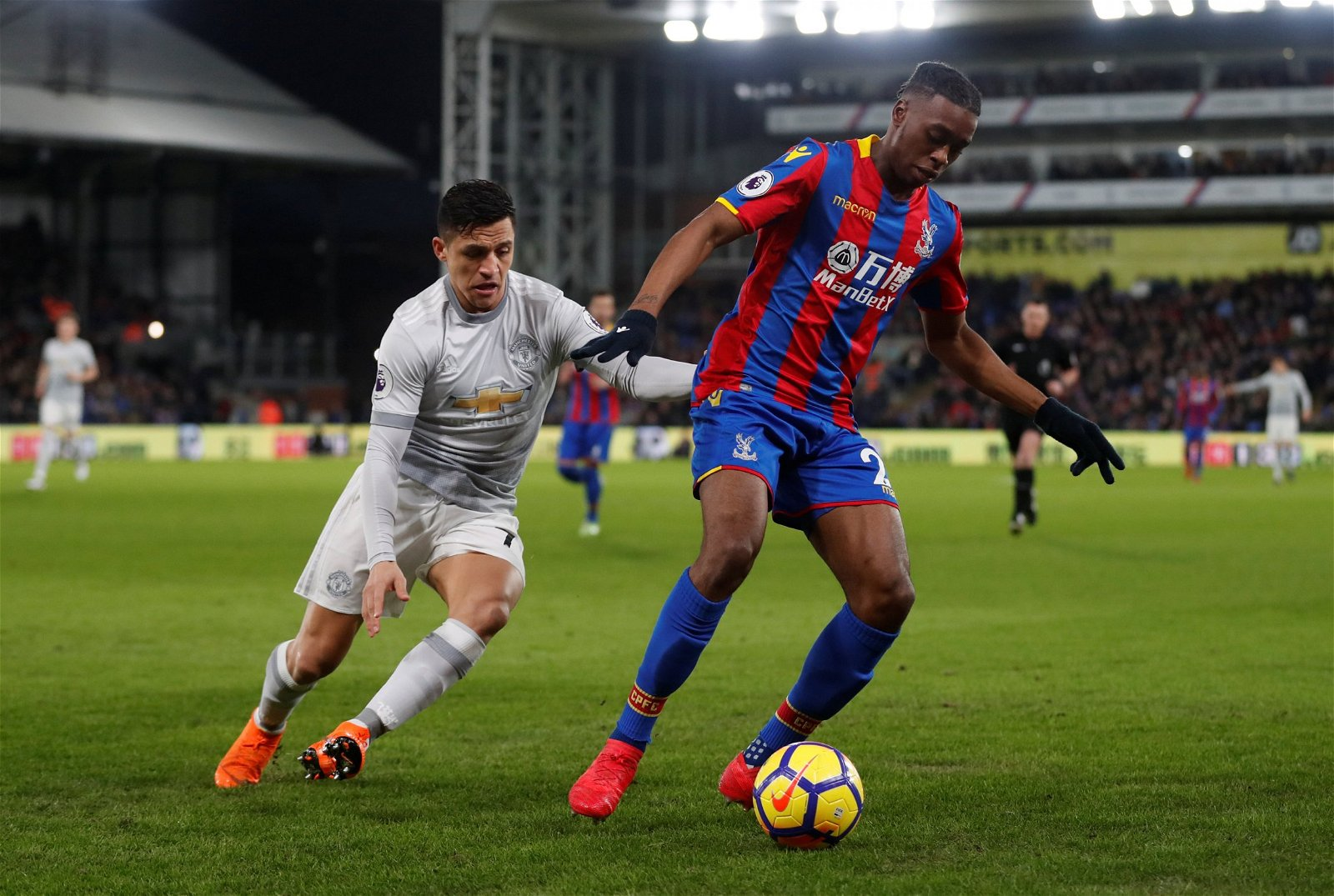 Aaron Wan Bissaka protects the ball from Alexis Sanchez