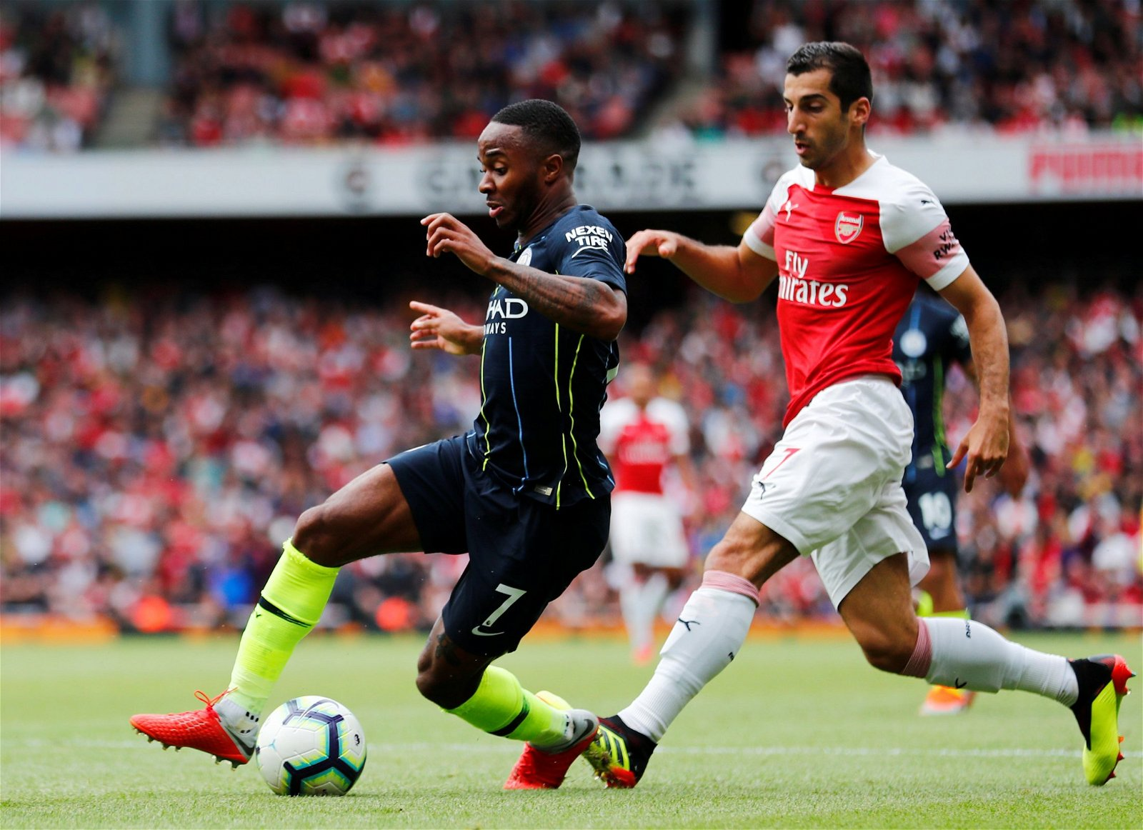Henrikh Mkhitaryan challenges Raheem Sterling for the ball