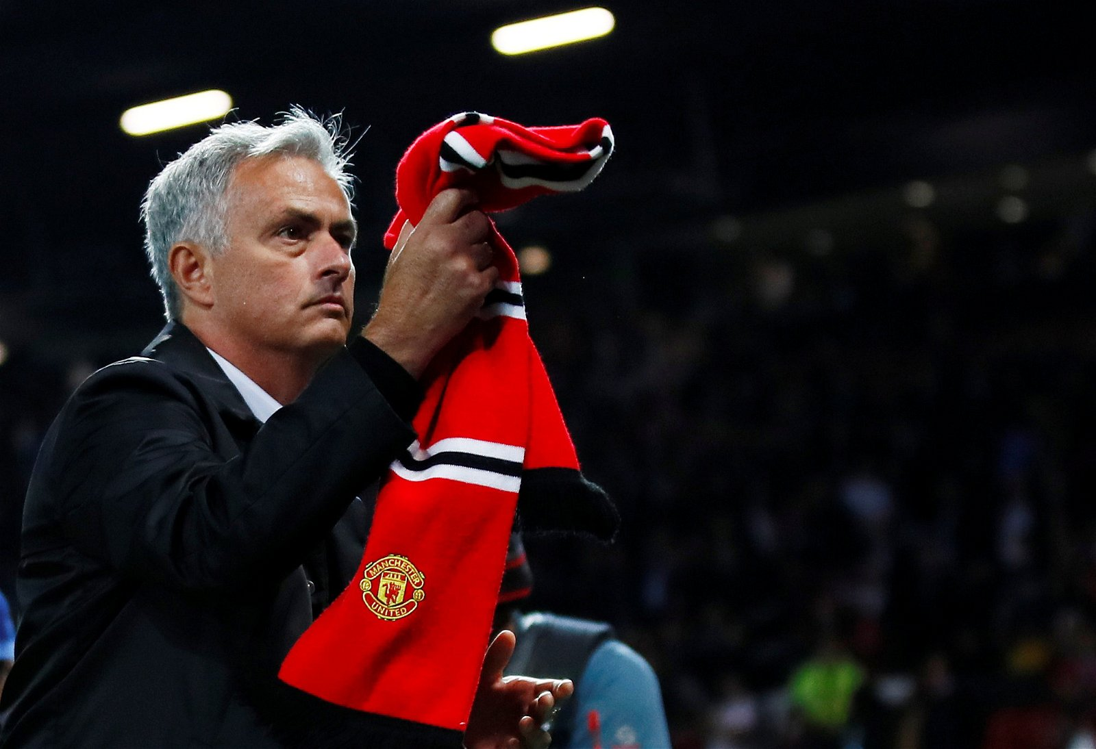Jose Mourinho takes a scarf from the Manchester United fans