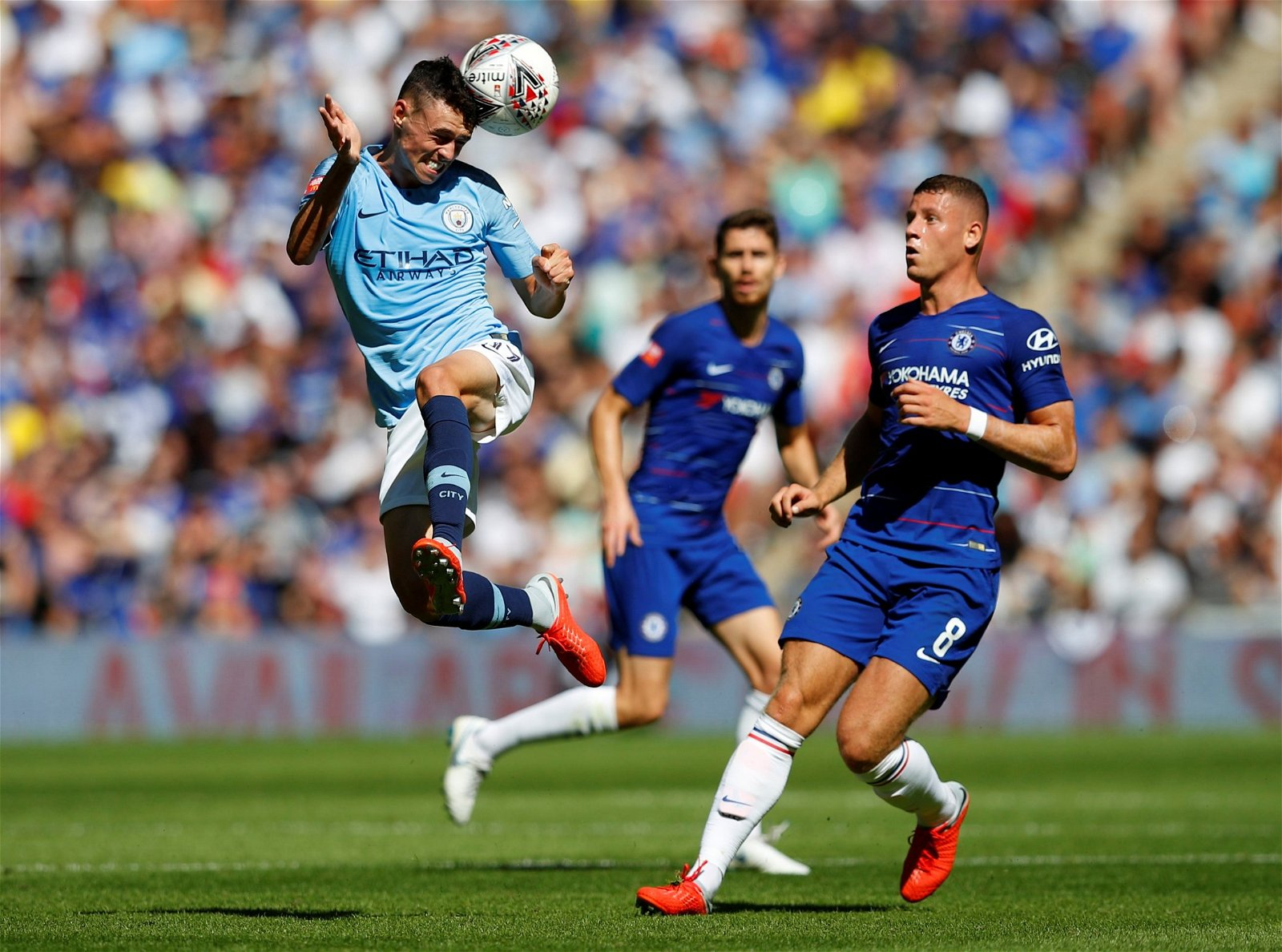 Phil Foden heads the ball away from Ross Barkley