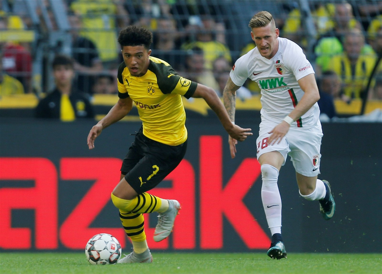 Jadon Sancho runs with the ball for Borussia Dortmund against Augsburg