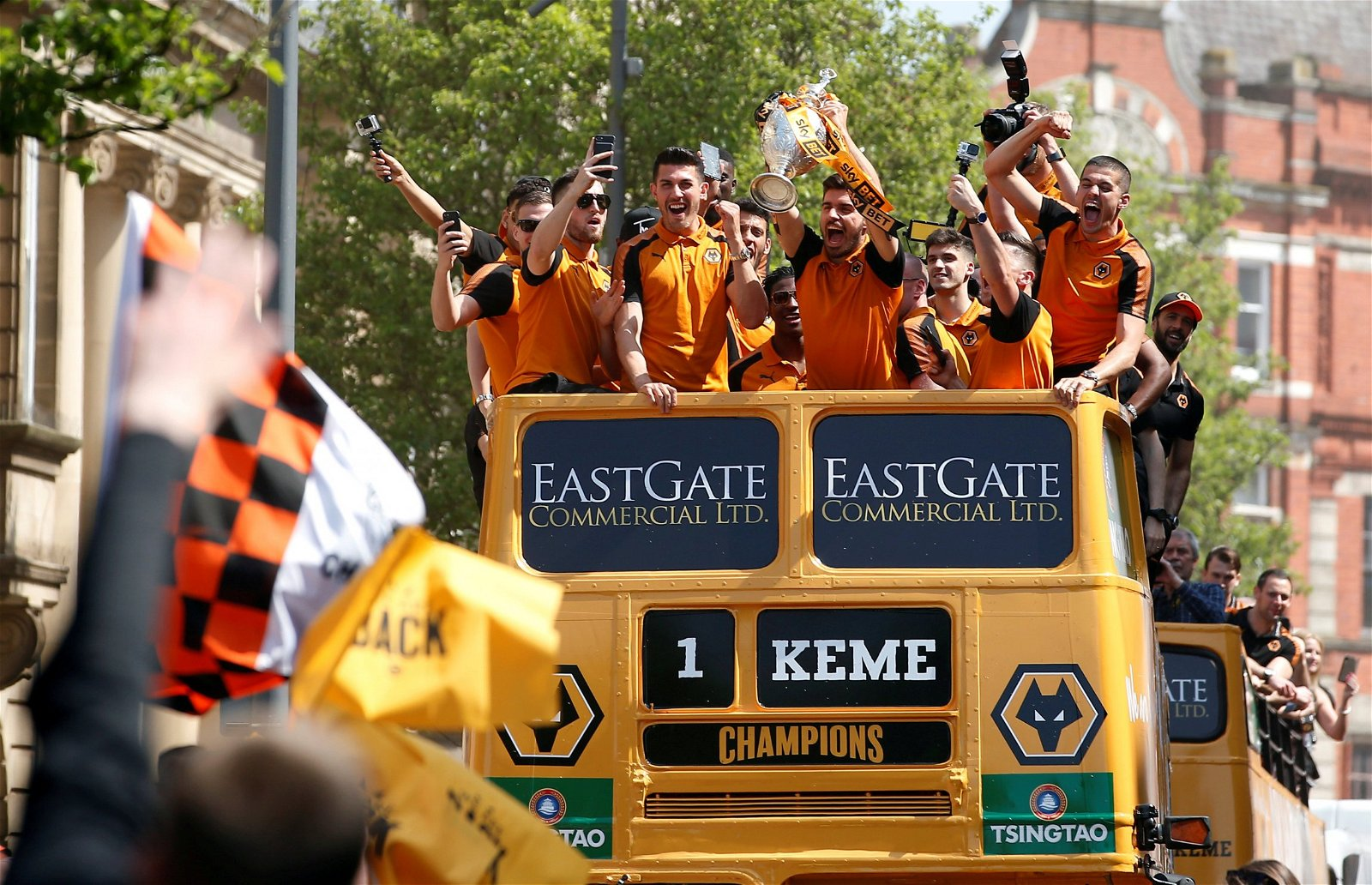 Wolverhampton Wanderers' Ruben Neves celebrates with the Championship trophy on the open top bus during the parade