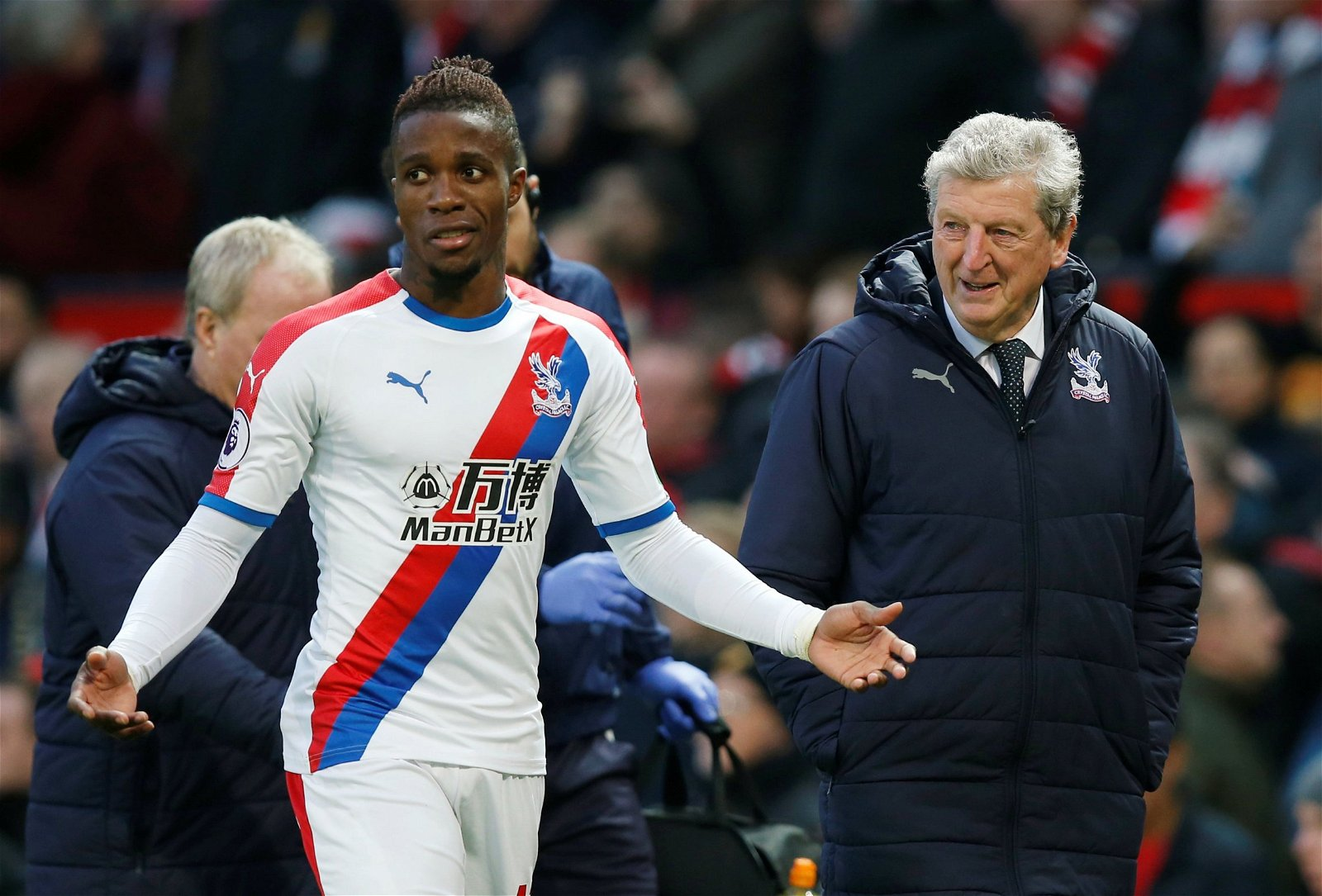 Crystal Palace's Wilfried Zaha and manager Roy Hodgson in discussion at half time at Manchester United