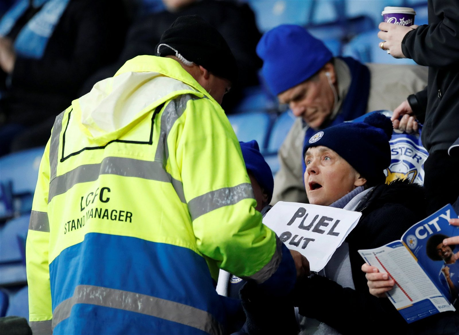 A Leicester City steward confiscates a sign saying 'Puel Out' from a fan before the Southampton match