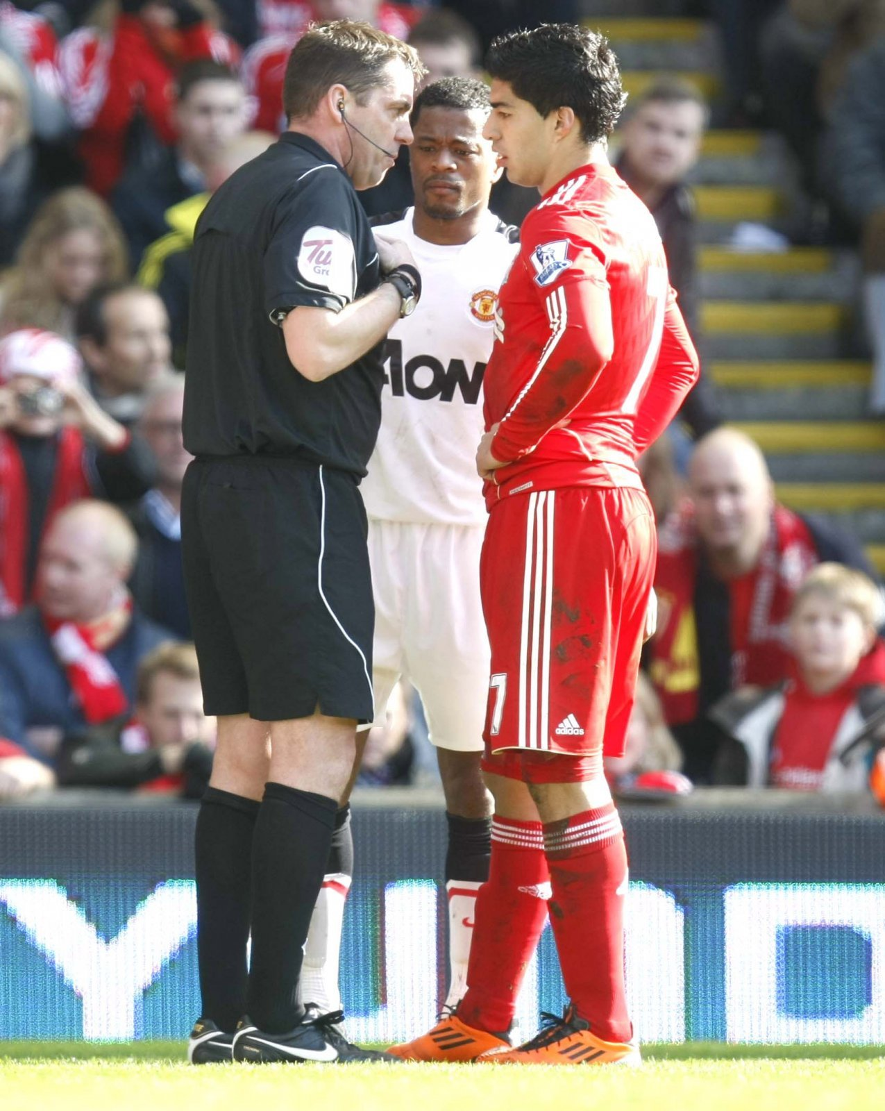 The referee talks to Luis Suarez and Patrice Evra