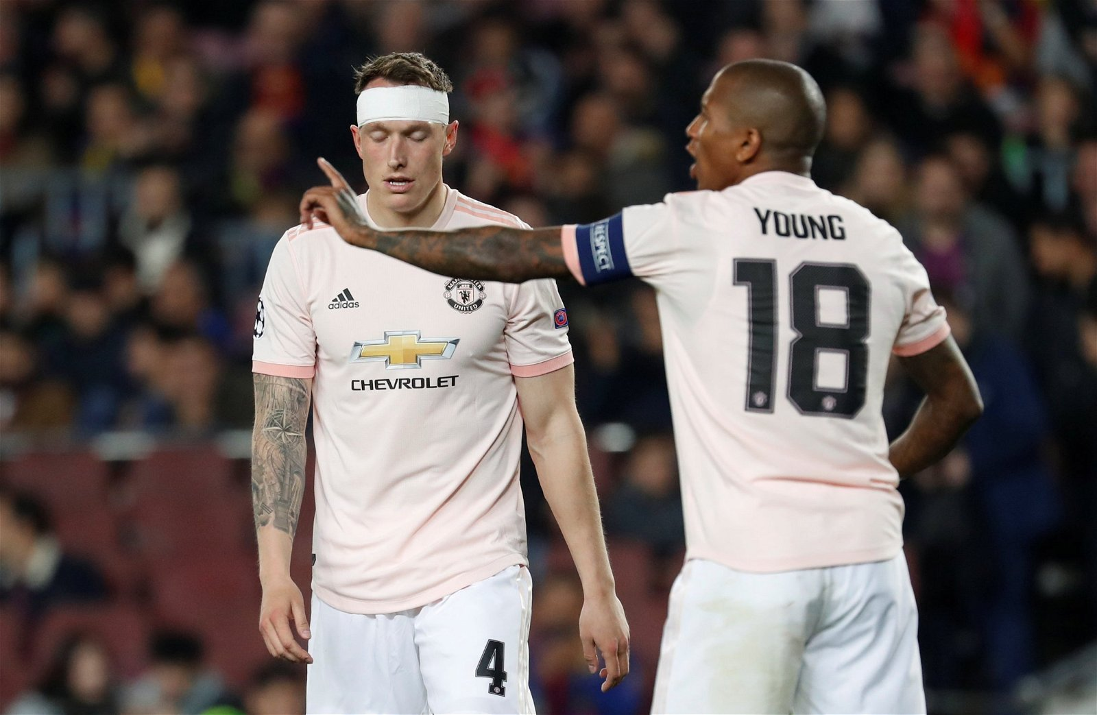 Man United defender Phil Jones looks dejected as Ashley Young points in Barcelona defeat